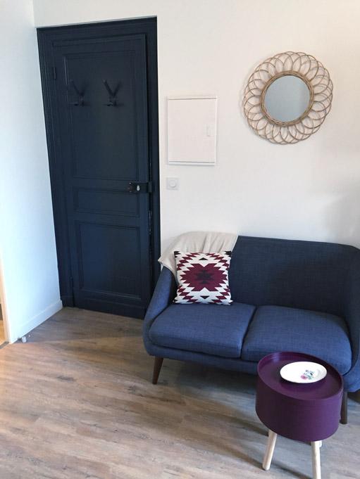 Studio Prune - Salon équipé à louer. Vue sur la partie salon avec un petit canapé et la porte d'entrée - Dax